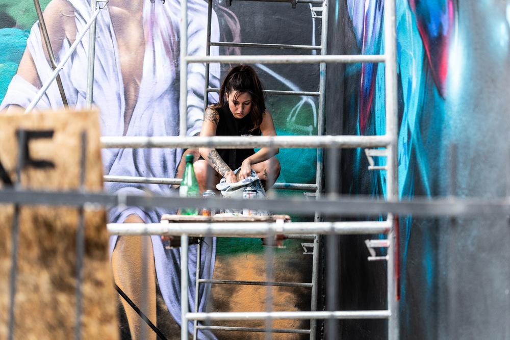 An artists sits upon a scaffolding, preparing to paint // Photo : Kieron Yates